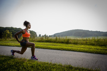 Young female runner stretching on rural park path
