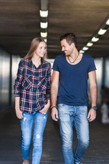 Young couple strolling in underpass
