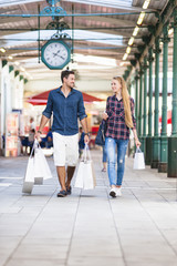 Young couple strolling with shopping bags in arcade