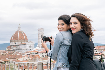 Lesbian couple taking photo of Florence Cathedral and Giotto's Campanile looking over shoulder smiling, Florence, Tuscany, Italy