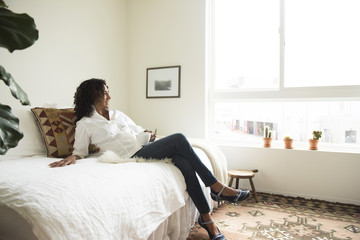 Mature woman relaxing on bed drinking coffee
