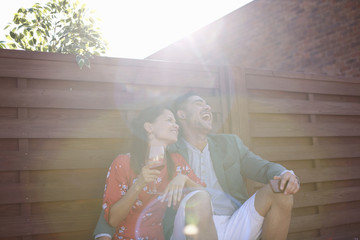 Relaxed mid adult couple laughing and drinking at rooftop party