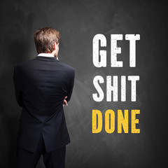 """Manager steht vor Wand mit Slogan """"Get Shit Done"""""""