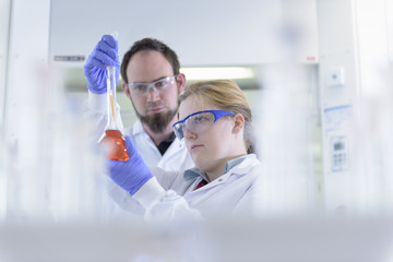Scientists inspecting coloured samples in testing laboratory
