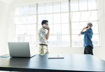 Businessmen speaking on smartphone by office window