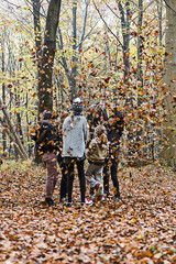 Girls playing with leaves in autumn forest