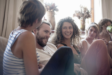 Group of friends, sitting on sofa, relaxing, smiling
