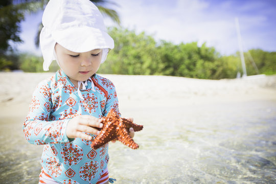 Girl on beach wearing swimwear and sunhat holding starfish looking down, St. Croix, US Virgin Islands