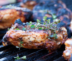 Chicken thighs with fresh thyme are being grilled on iron grates over charcoal