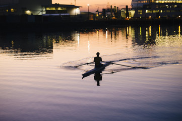 Young man rowing on river at sunset