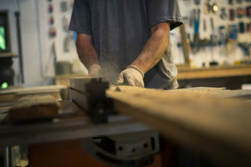 Wood artist in workshop, using woodworking machinery, mid section