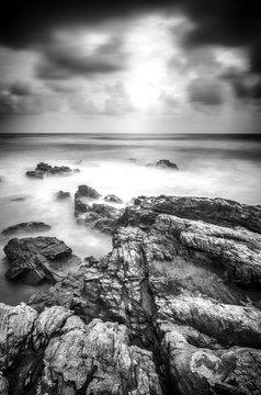 black and white image soft wave hitting the rock along the coastline.