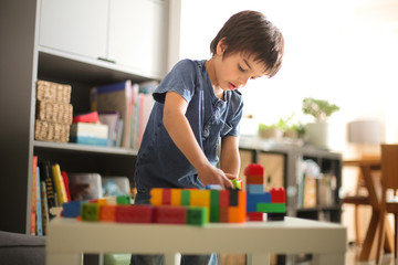 Boy at home looking down playing with colourful building blocks