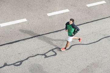 High angle view of young male runner running along parking lot