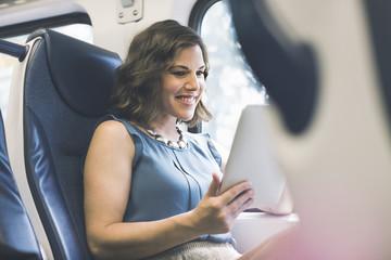 Mid adult woman on train using digital tablet
