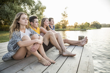 Group of friends sitting on jetty, relaxing