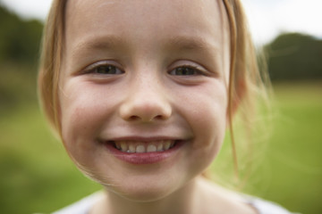 Portrait of young girl in field, smiling, close-up