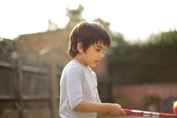 Side view of boy holding toy balancing tennis ball