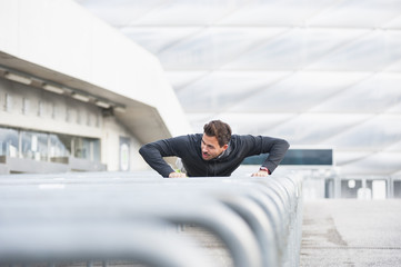 Young male runner doing push ups on sport arena handrails