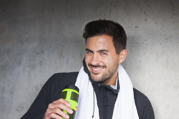 Portrait of happy young male runner leaning against wall with water bottle