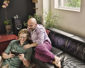 Romantic male couple reclining on sofa looking at digital tablet