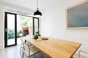 Scandi styled dining room interior with outlook to courtyard via