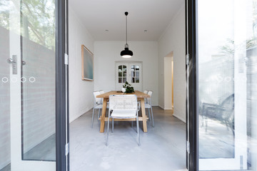 Looking into contemporary dining room through french doors from