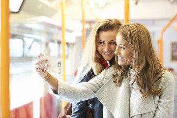 Two young female friends on train, taking self portrait, using  smartphone