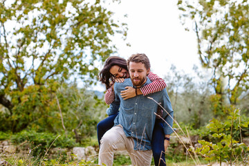 Young man giving girlfriend a piggy back in olive grove, Florence, Italy