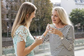 Women outdoors holding coffee cups face to face smiling