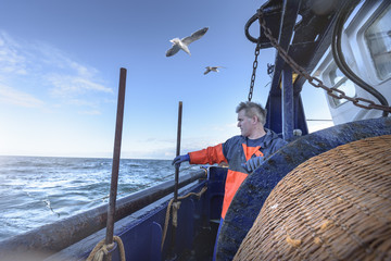 Fisherman looking out to sea on trawler