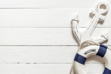 Anchor and lifebuoy on white wood table