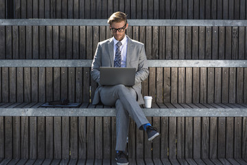 Suited young businessman typing on laptop on city stair