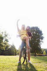 Young couple on bicycle taking smartphone selfie in sunlit park