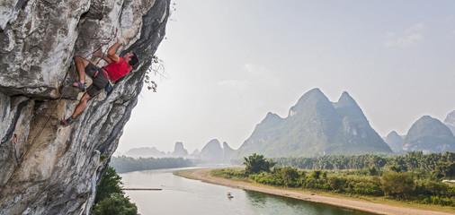 Male climber climbing Riverside crag in Yangshuo, Guangxi Zhuang, China