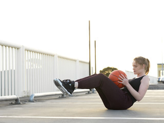 Young female basketball player doing sit-ups in parking lot