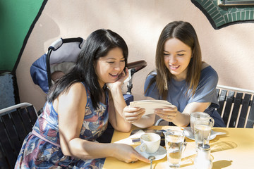 Young woman with mother and baby daughter looking at photographs at sidewalk cafe