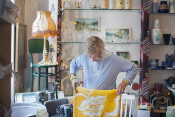 Mature woman folding yellow blanket in vintage shop