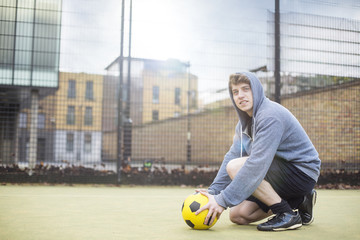 Young man setting football on floor, on urban football pitch