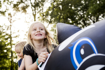 Two sisters playing on inflatable whale in park