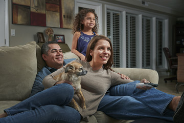 Parents and girl in living room on sofa with dog looking away smiling