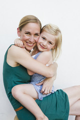 Portrait of mid adult woman with daughter sitting on lap in front of white wall