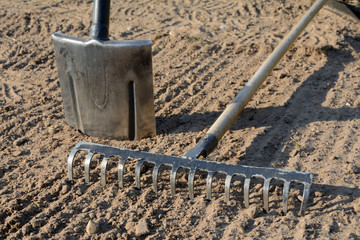 Rake and spade on soil