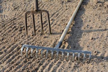 Rake and pitchfork on soil