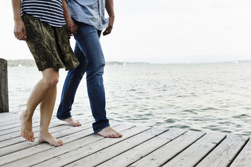 Cropped view of romantic couple strolling on wooden pier, Lake Starnberg, Bavaria, Germany