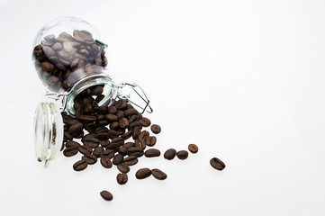 Roasted coffee beans in a jar on white background