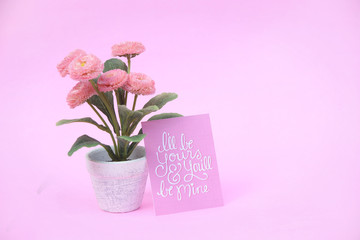 Flower pot with paper note on the pink background