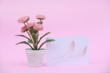 Flower pot with blank paper note on the pink background