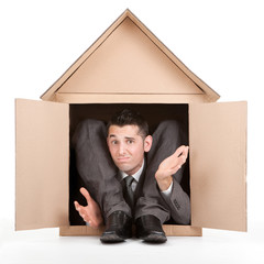 elegant disappointed flexible contortion businessman in cardboard house