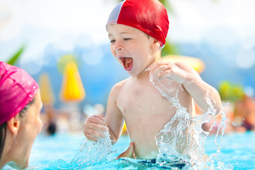 happy child and mom with swimming pool cap have fun in a pool